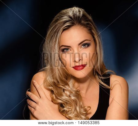 beautiful model with curly blond hair on dark background