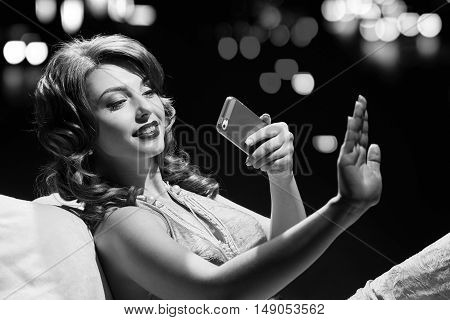 woman in dress studio portrait in hollywood style light with night lights city background. making photo her manicure. in black and white toning