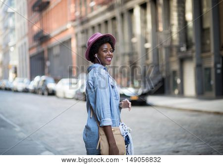 Portrait of young African American woman listening to music on city street. Photographed in Soho NYC.