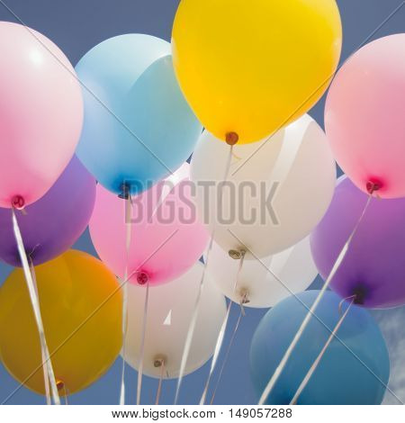 Vintage tone of coloured balloons over the blue sky