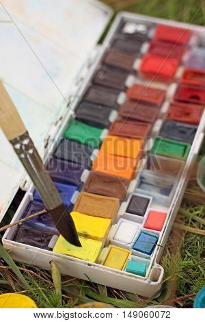 box of watercolors with a brush on the grass