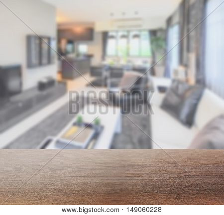 wooden table top with blur image of modern living room interior with dining table and pantry at home