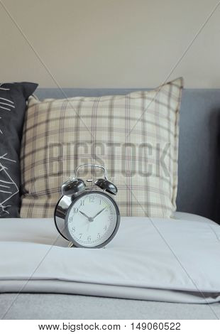 Alarm Clock And Graphic Pattern Pillows On Bed