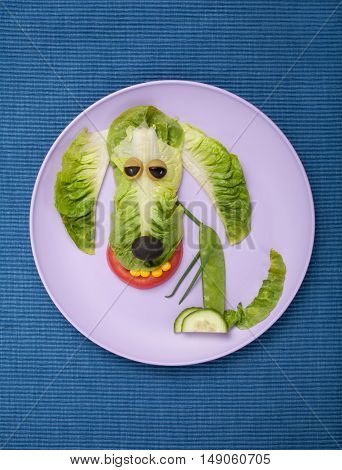 Happy dog made of salad on plate and fabric