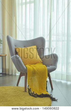 Yellow Scraft And Yellow Pillow Setting On Gray Color Easy Armchair In Living Room