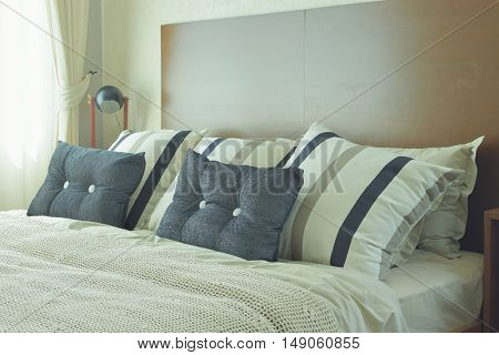 Gray And Brown Strip Pillows Setting On White Linen Bedding With Brown Wooden Headboard