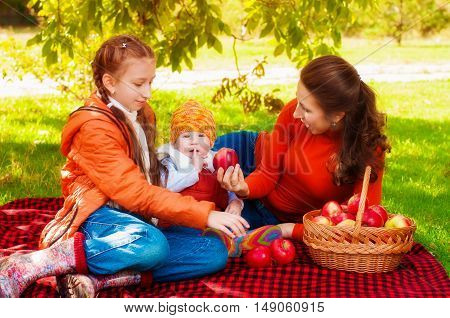 Family with mother and children in the park in autumn with a basket of apples