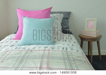 Light Blue And Pink Pillow On Sweet Bedding And Picture Frame On Bedside Table