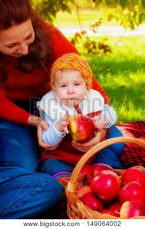 Young mother and little son in the park in autumn with a basket of apples