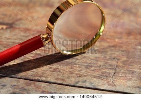 Magnifying glass with long shadow on wooden background