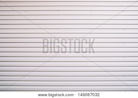 Metal gray shutter door texture, close-up. Steel rolling gate with horizontal lines, aluminium planks with screws