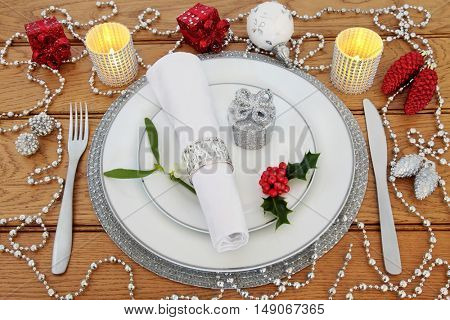 Christmas dinner table setting with white porcelain plates, knife and fork, linen serviette, holly, mistletoe, candles and  bauble decorations over oak background.