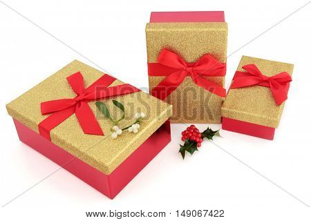 Christmas gold glitter gift boxes with red bows with holly and mistletoe on white background.