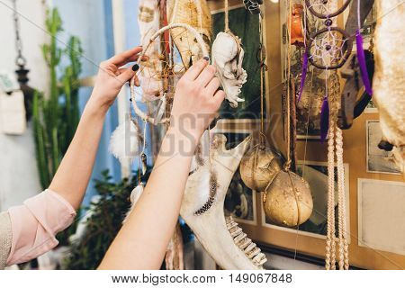 Artisan hanging new dream catcher to other creations. Art installation of decorative elements and animal bones. Craftsman exhibition