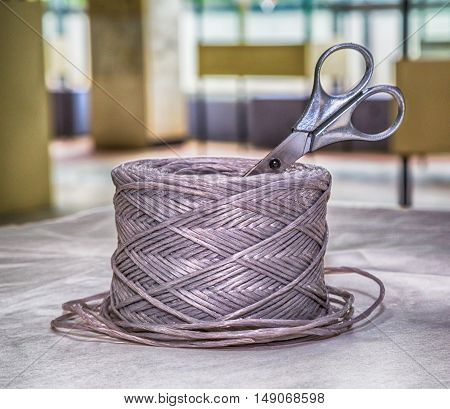 coil of rope and scissors on a white surface twine roll link domestic interior