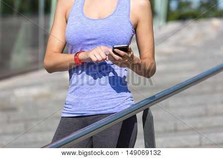 Sportive woman leans on a handrail and checks her fitness results on a smartphone. She wears a fitness tracker wristband on her left arm. Unfiltered version