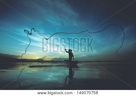 Silhouette of fishermen using nets to catch fish at the lake in the morning