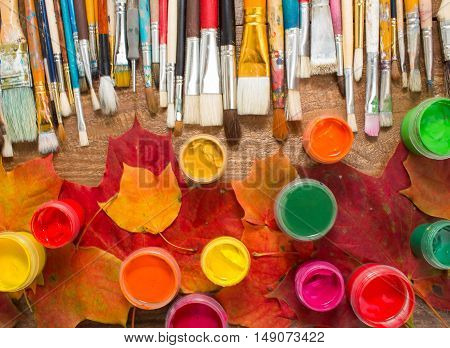 Paints, brushes, autumn leaves on wooden background.Autumn still-life. The workplace of the artist. Banner for the school.