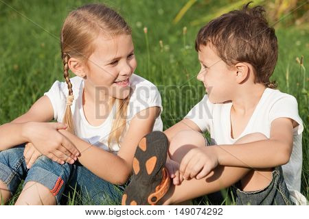 Two happy children playing near a tree on the grass at the day time. Concept Brother And Sister Together Forever