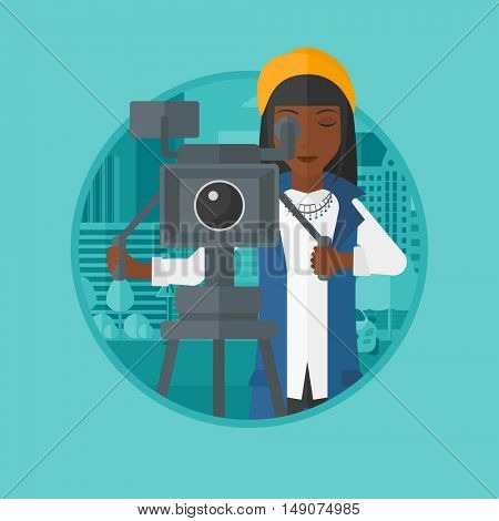An african-american cameraman looking through movie camera on a tripod. Woman with professional video camera shooting in the city. Vector flat design illustration in the circle isolated on background.