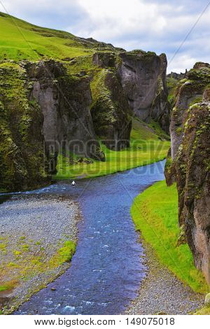 Canyon Fjadrargljufur and cold fast river with a pebble bottom. Iceland in the summer