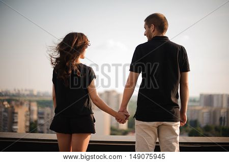 couple from behind holding hands looking on city view