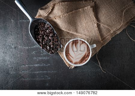 Coffee cup and coffee bean on black stone background