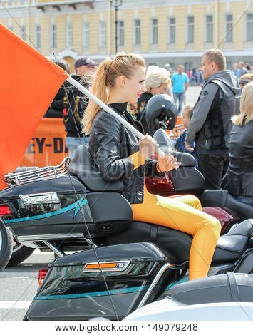 St. Petersburg, Russia - 12 August, Girl with a flag on a motorcycle,12 August, 2016. The annual International Festival of Motor Harley Davidson in St. Petersburg Ostrovsky Square.
