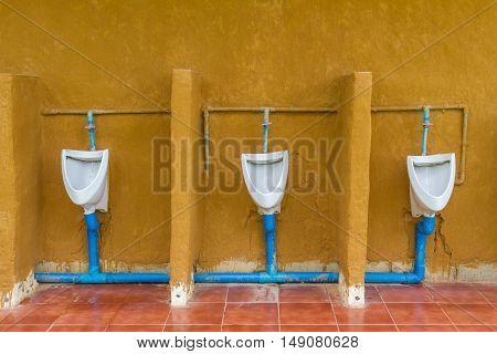 Three Urinals Men public in toilet room