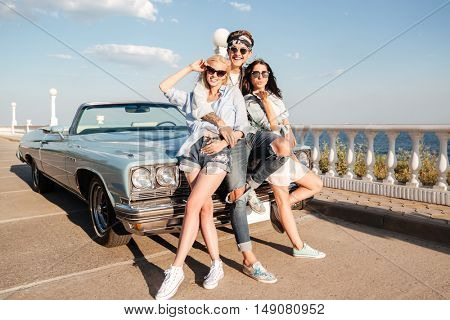 Full length of cheerful young man and two happy women standing near vintage cabriolet in summer