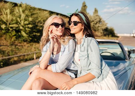 Two cheerful attractive young women sitting on car and smiling