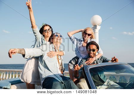 Group of cheerful young friends sitting and relaxing in car