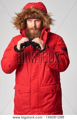 Portrait of a man wearing red winter jacket with fur hood on with binoculars, studio shot