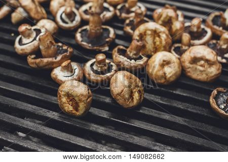 Mushroom barbecue roasted on metal grill. Diet vegan bbq. Fungi kebab closeup at picnic outdoors