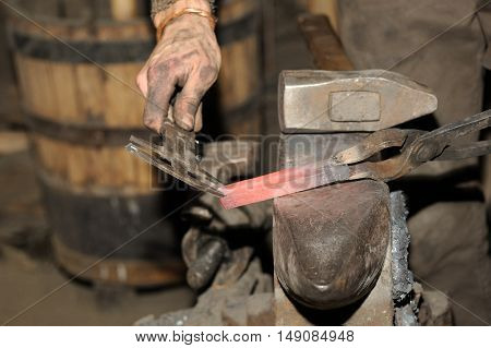 Blacksmith Working In The Forge Processes The Metal .