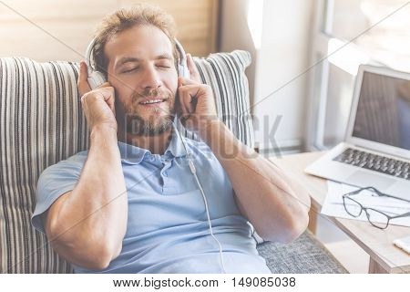 Handsome young businessman in casual clothes is listening to music in headphones while lying with closed eyes on couch at home