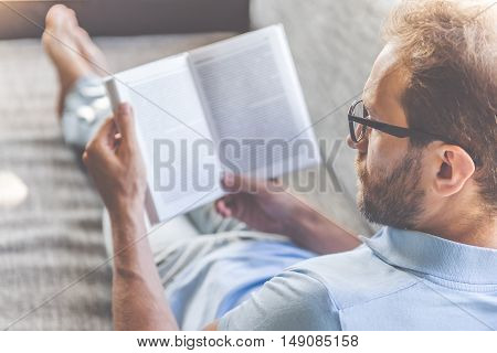 Back view of handsome young businessman in casual clothes and eyeglasses reading a book while lying on couch at home