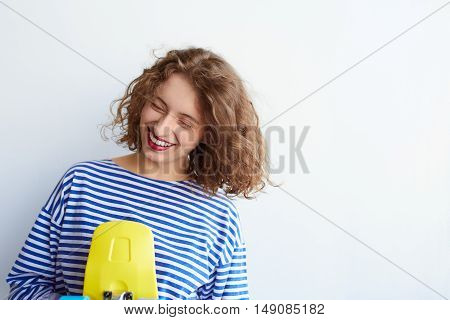 Positive indoor portrait of hipster woman having fun, happy emotions, trendy striped clothes, curly hair, positive mood, white wall bright colors. holding yellow skateboard with copyspace