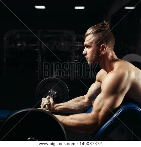 Bodybuilder in the gym. Muscular man working out doing exercises with barbell at biceps, strong male naked torso in the gym. Handsome bodybuilder with big muscles, posing at the camera in the gym