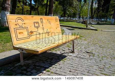 unusual bench in the park. bench in the form of a keyboard with the possibility of charging gadgets
