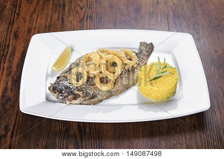 on the table a plate of grilled fish trout with lemon fried onion rings with sesame seeds and as a garnish rice and rosemary.