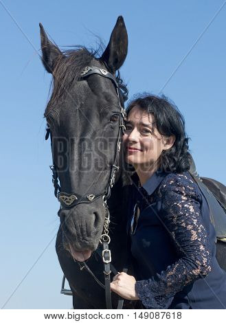 girl with a black stallion in a field