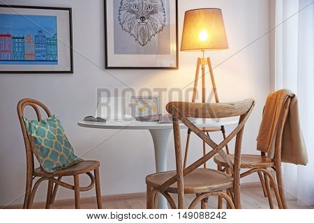 Modern white table, floor lamp and wooden chairs near wall