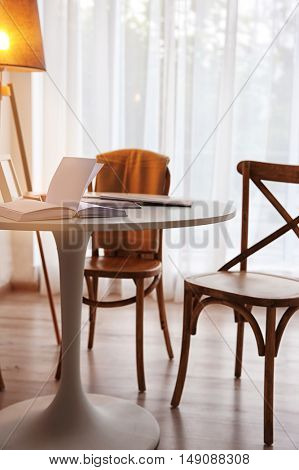 Modern white table, floor lamp and wooden chairs near window