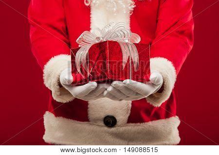 christmas Photo of kind Santa Claus giving xmas present and looking at camera