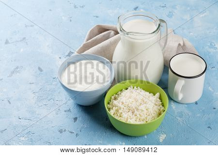 Dairy products on stone table. Sour cream, milk and curd cheese. View with copy space
