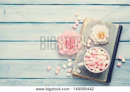 Marshmallow in coffee cup over old book on wooden table. Top view with copy space for your text. Toned