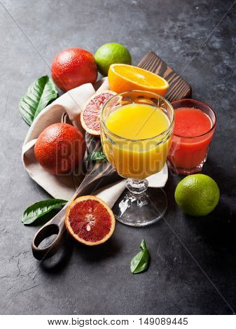 Fresh citruses and juice on dark stone background. Oranges and limes