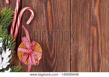 Christmas gingerbread cookies, candy cane and tree branch on wooden table. Top view with copy space