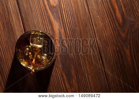 Glass of whiskey with ice on wooden table. Top view with copy space